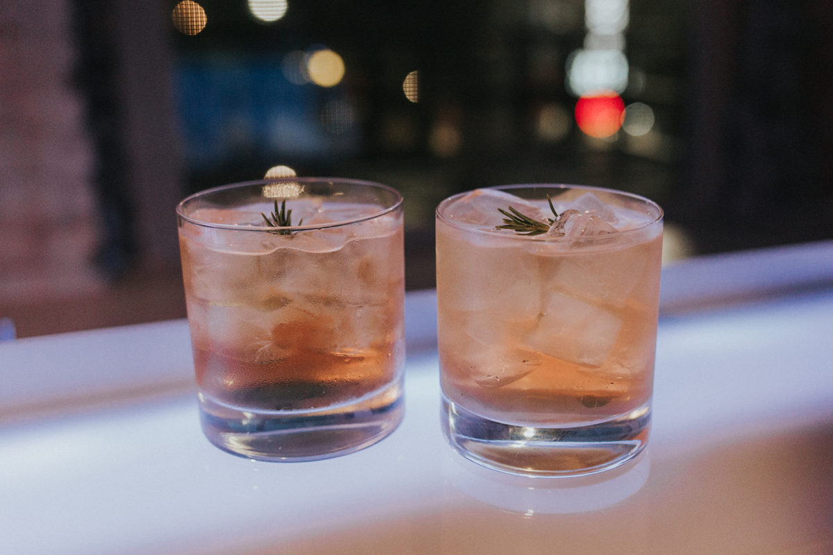 whiskey rose cocktail with rosemary, lemon, and sparkling apple soda